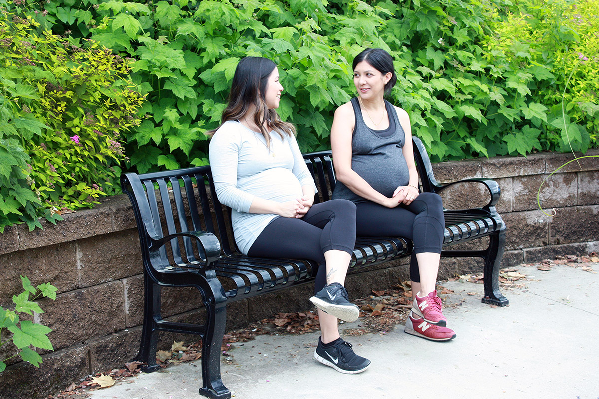 2 pregnant women sitting on a park bench